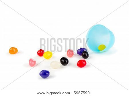 Colorful jelly beans spilled out of a plastic Easter egg.