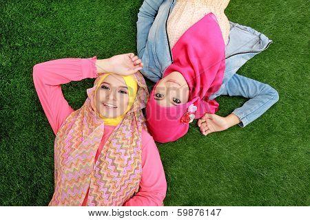 Close Up Two Beautiful Happy Muslim Woman Lying On Grass