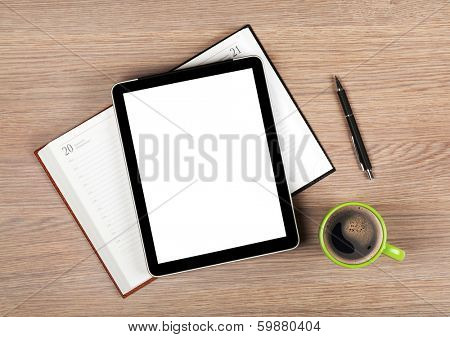 Tablet with blank white screen and coffee cup on office wooden table