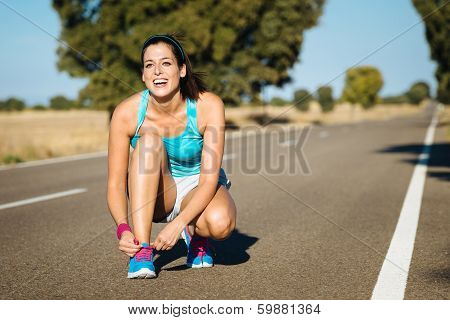 Woman Tying Sportshoes Laces For Running