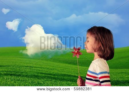 Beautiful girl blowing a windmill to make heart shape clouds