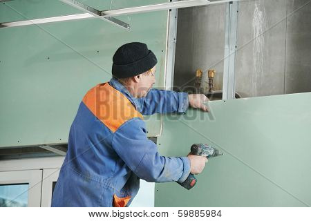 Carpenter joiner plasterer with screwdriver mounting gypsum plasterboard system at toilet