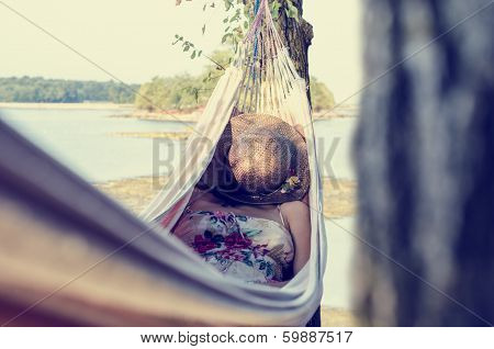 Woman Relaxing In A Hammock, Next To A Sea