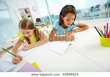 Portrait of lovely schoolgirls drawing at workplace with schoolmate on background