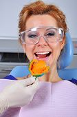 stock photo of dental impression  - woman in dentist chair with dental impression tray in her mouth - JPG