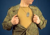 stock photo of open shirt breast showing  - Military man opens his shirt space for text - JPG