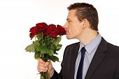Young man sniffs scent of roses