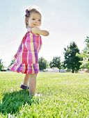 a cute girl running in a local park giggling at the camera