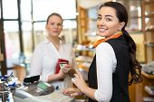 stock photo of cash  - Client at shop paying at cash register with saleswoman - JPG