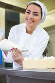 image of confectioners  - Female baker or confectioner prepares cake with whipped cream
