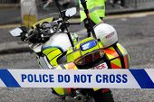 stock photo of criminology  - Policeman and police motorcycle behind cordon tape at an accident or crime scene - JPG