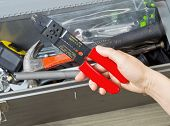 stock photo of wire cutter  - Horizontal photo of female hand taking out electrical wire cutters from used toolbox with aged wooden floors underneath - JPG