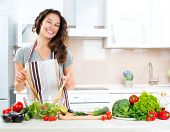 stock photo of vegan  - Young Woman Cooking in the kitchen - JPG