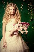 foto of loach  - Lovely girl in a lush white dress stands under a floral arch over green background - JPG