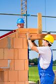 picture of bricklayer  - Two bricklayers or builders or workers building or bricklaying or laying a stone or brick wall on a construction or building site - JPG