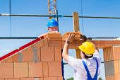 stock photo of bricklayer  - Two bricklayers or builders or workers building or bricklaying or laying a stone or brick wall on a construction or building site - JPG