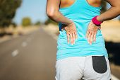 picture of muscle strain  - Female runner athlete back injury and pain - JPG
