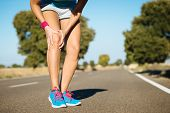 stock photo of hurt  - Female runner sport knee injury and pain - JPG