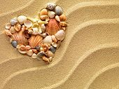 image of holiday symbols  - Heart made of sea shells and the starfish lying on a beach sand summer background - JPG