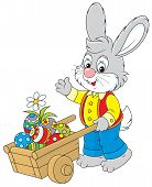 stock photo of cony  - Rabbit walking with a hand cart filled with colorfully painted Easter eggs - JPG