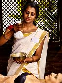 stock photo of panchakarma  - India woman taking massage  pouch of rice - JPG