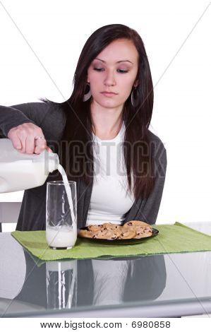 Menina bonita, derramando o leite ao seu vidro