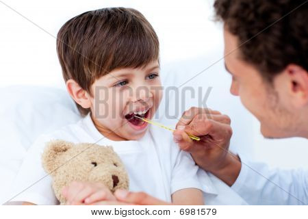 Male Doctor Taking Little Boy's Temperature