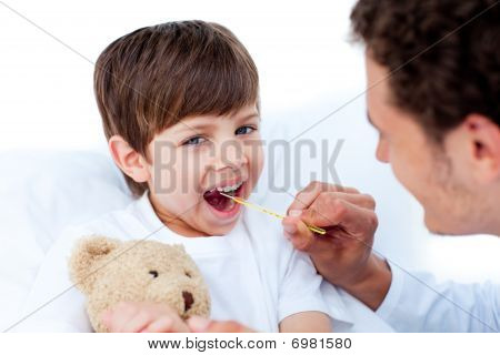 Young Doctor Taking Little Boy's Temperature