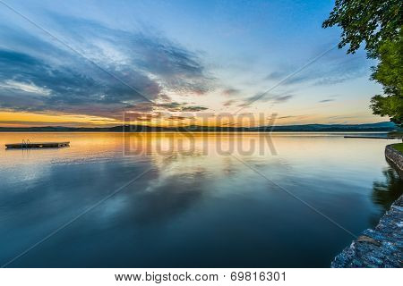 blue golden sunset at lake wallersee with reflection in water