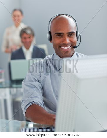 Confident  Businessman With Headset On Working At A Computer