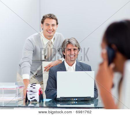 Smiling Businessmen Working At A Computer Together