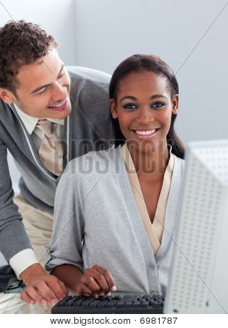 Young Businessman Helping His Colleague At A Computer