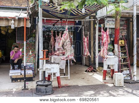 Butcher's Shop With Fresh Raw Meat Hanging On The Pavement.