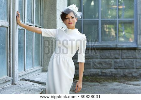 Wedding. Beautiful woman in stylish sheath dress on a background of old building.