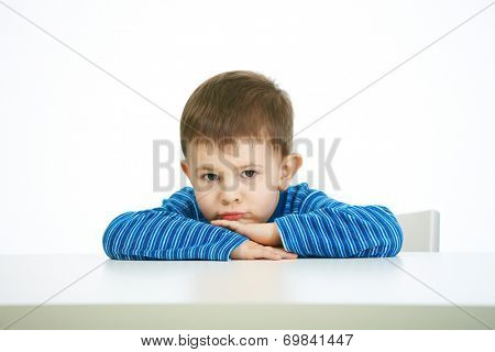 Portrait of sullen little boy sitting at table, looking at camera, serious.