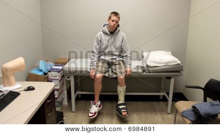 A Boy in a Leg Cast Sits, Awaiting the Doctor