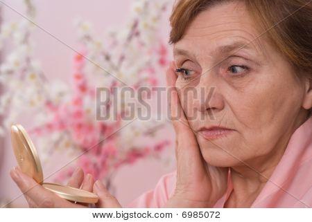 Pretty  Elderly Woman Looks In The Mirror