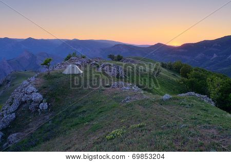 Mountain landscape with a beautiful sunset. Camping in the outdoors with a tent