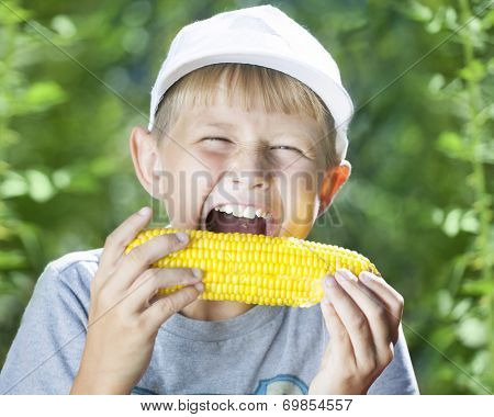 boy eating a hot summer corn