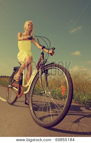 Young girl in yellow dress riding a retro style bike.