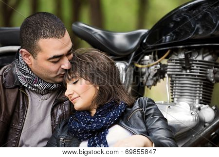 Attractive woman sleeping on shoulders of her husband, sitting near bike, relaxation after bikers tour in the forest, active and loving family concept