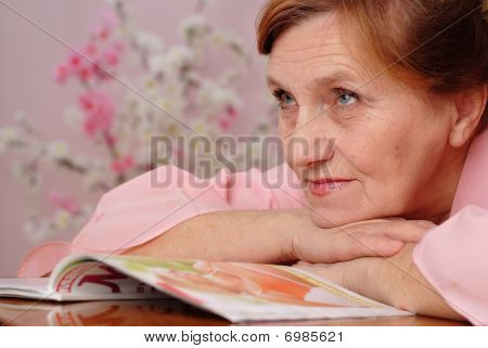 Pretty  Elderly Woman Looks In The Mirror
