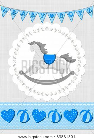 Baby boy toy animal rocking horse on white doily with flag banner and ribbon