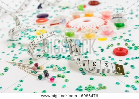 Sewing Background: Buttons, Bobbins, Ruler, Needles And Beads