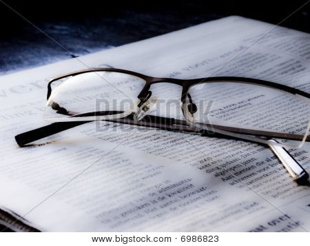 Pair of reading glasses on newspaper
