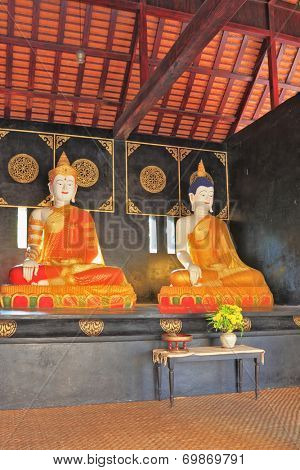 NORTHERN THAILAND - APRIL 14, 2011: Two statues of the Buddha under canopy. The statues dressed in gilded clothing