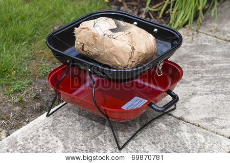 Portable BBQ with unlit instant charcoal.