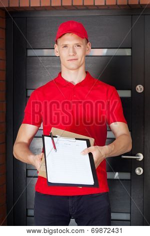 Young Delivery Man With Clipboard And Package