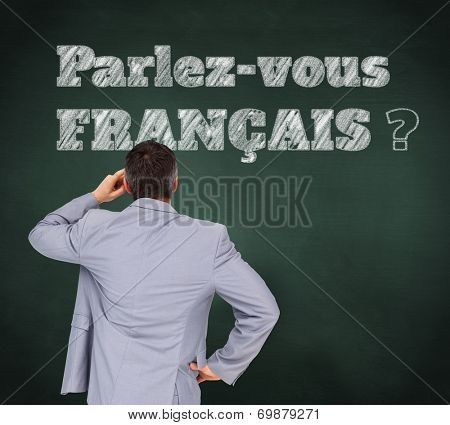 Thinking businessman against green chalkboard, Do you speak French?