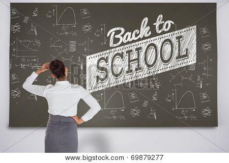 Composite image of businesswoman scratching her head against black chalkboard